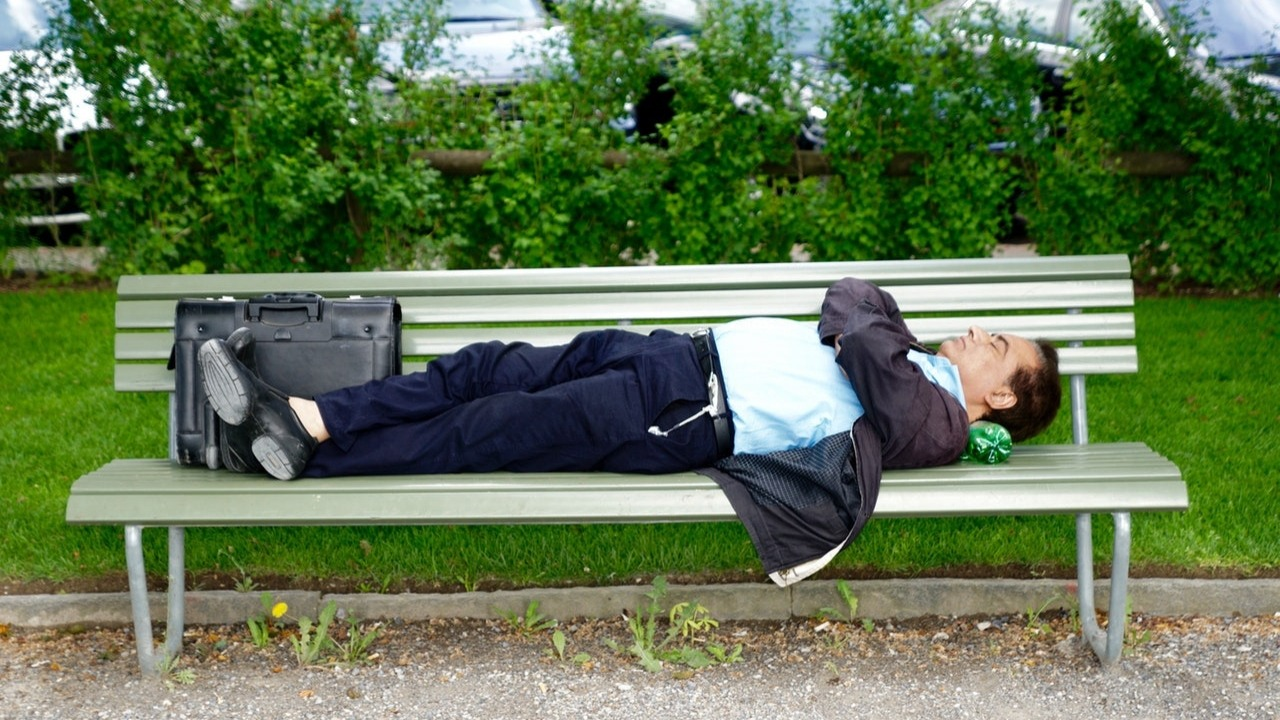 man sleeping on a bench in soldier position