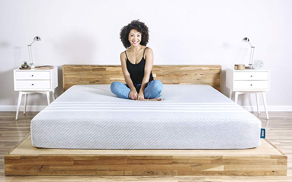 woman sitting happily on a leesa mattress