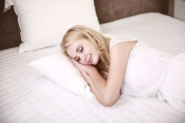woman smile while sleeping on a bed