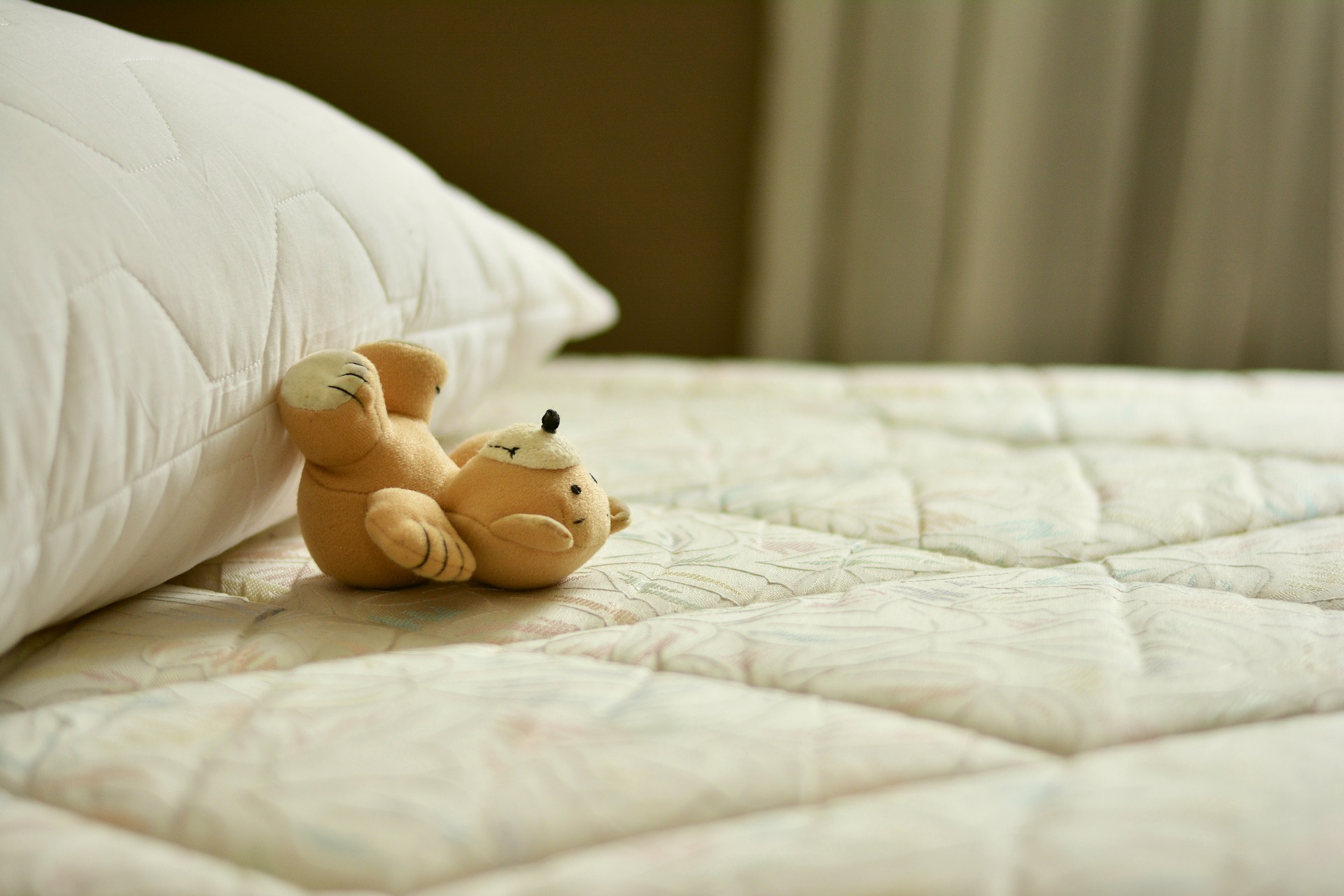 Stuffed toy and pillow at the top of the best mattress for side sleeper